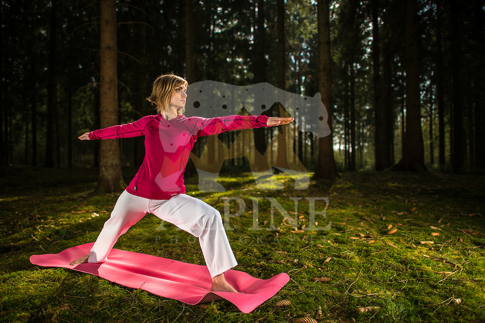 A female athlete practices yoga stances on a warm and sunny Spring day in the forests of Diever, Drenthe, Netherlands.