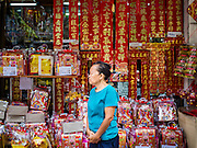 "04 FEBRUARY 2016 - BANGKOK, THAILAND:  A vendor selling Chinese New Year decorations waits for customers in Bangkok's Chinatown district, before the celebration of the Lunar New Year. Chinese New Year, also called Lunar New Year or Tet (in Vietnamese communities) starts Monday February 8. The coming year will be the ""Year of the Monkey."" Thailand has the largest overseas Chinese population in the world; about 14 percent of Thais are of Chinese ancestry and some Chinese holidays, especially Chinese New Year, are widely celebrated in Thailand.     PHOTO BY JACK KURTZ"