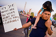 03 APRIL 2008 -- GUADALUPE, AZ:  TONY MORENO and his daughter, KAYLEE MORENO hold up a sign in on a street in Guadalupe, AZ, a suburb of Phoenix, in opposition to Sheriff Joe Arpaio and the crime sweep deputies conducted in Guadalupe Thursday. The sign is a reference to a double stabbing that took place over the weekend a few miles from Guadalupe. Guadalupe is a working class unincorporated town south of Phoenix. Most of the town's residents are Native Americans and Hispanics and hundreds of people lined the street to protest the sweep.   In 2011, the US Department of Justice issued a report highly critical of the Maricopa County Sheriff's Department and the jails. The DOJ said the Sheriff's Dept. engages in widespread discrimination against Latinos during traffic stops and immigration enforcement, violates the rights of Spanish speaking prisoners in the jails and retaliates against the Sheriff's political opponents.     PHOTO BY JACK KURTZ