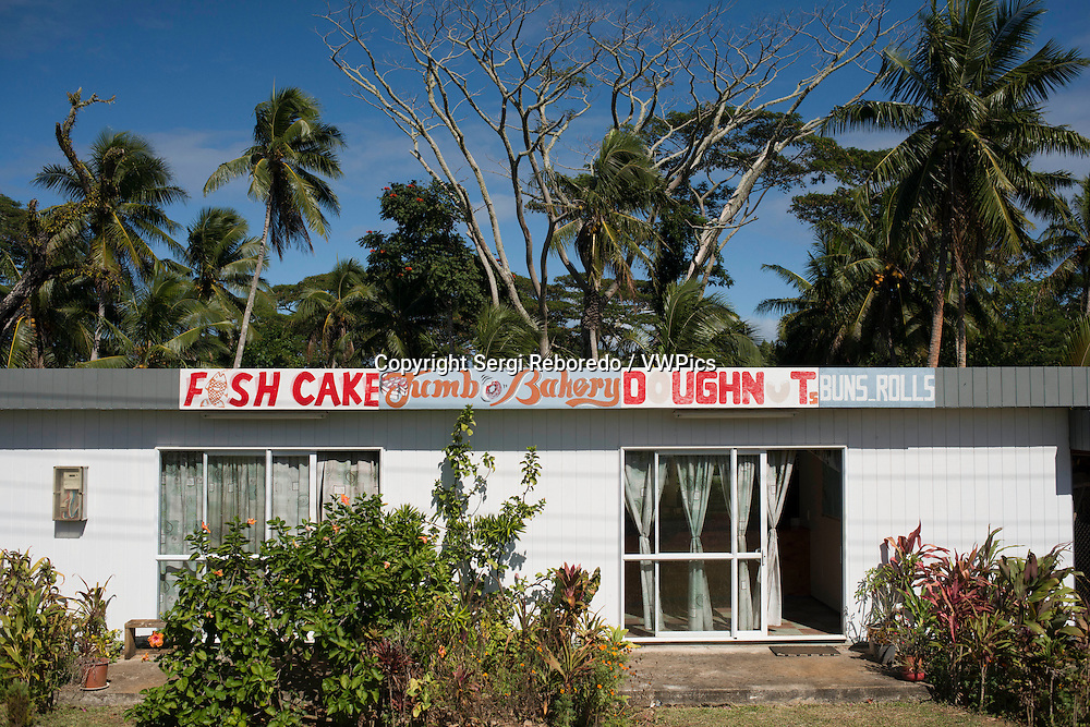 Fish Cake Bakery shop in Atiu Island. Cook Island. Polynesia. South Pacific Ocean. Shopping on Atiu is limited to the small number of general stores and their basic food supplies. All shops are closed on Sundays.<br /> <br /> Our Artists and galleries page has information about the small but exciting art and craft produced on Atiu and opportunities for buying these.<br /> <br /> The general stores sell a range of basic food and general supplies. Because of the extra cost of freight prices tend to be expensive compared to Rarotonga which many visitors find expensive enough. All of which means that the cost of goods is especially high for locals who generally have minimal incomes. But these shops are interesting to explore and to see what general goods are needed on small islands.