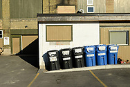 Garbage and recycle bins line up behind Worth a Second Look, a second hand store in Kitchener, Ontario, Canada. WASL, as it is sometimes called, is a business that is part of The Working Centre, a social enterprise.