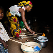 Marie Madeleine Ouattara cooking toh, a local staple made from millet, for the midday meal in the village of Toussiana in the Hauts-Bassins region of Burkina Faso, on 22 February 2016. She lives in an extended family household, and she and her husband's brother's wife take it in turns to cook.