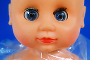 Close up of a doll's face with wide open blue eyes against blue background
