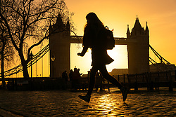 © Licensed to London News Pictures. 22/12/2018. London, UK.  A woman walks along the Thames path next to Tower Bridge shortly after sunrise, as the capital is experiencing milder and sunny weather this morning.  Photo credit: Vickie Flores/LNP