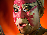 """26 NOVEMBER 2014 - BANGKOK, THAILAND: A performer warms up before going on stage in a Chinese opera at the Chow Su Kong Shrine in the Talat Noi neighborhood of Bangkok. Chinese opera was once very popular in Thailand, where it is called """"Ngiew."""" It is usually performed in the Teochew language. Millions of Chinese emigrated to Thailand (then Siam) in the 18th and 19th centuries and brought their culture with them. Recently the popularity of ngiew has faded as people turn to performances of opera on DVD or movies. There are about 30 Chinese opera troupes left in Bangkok and its environs. They are especially busy during Chinese New Year and Chinese holidays when they travel from Chinese temple to Chinese temple performing on stages they put up in streets near the temple, sometimes sleeping on hammocks they sling under their stage.      PHOTO BY JACK KURTZ"""
