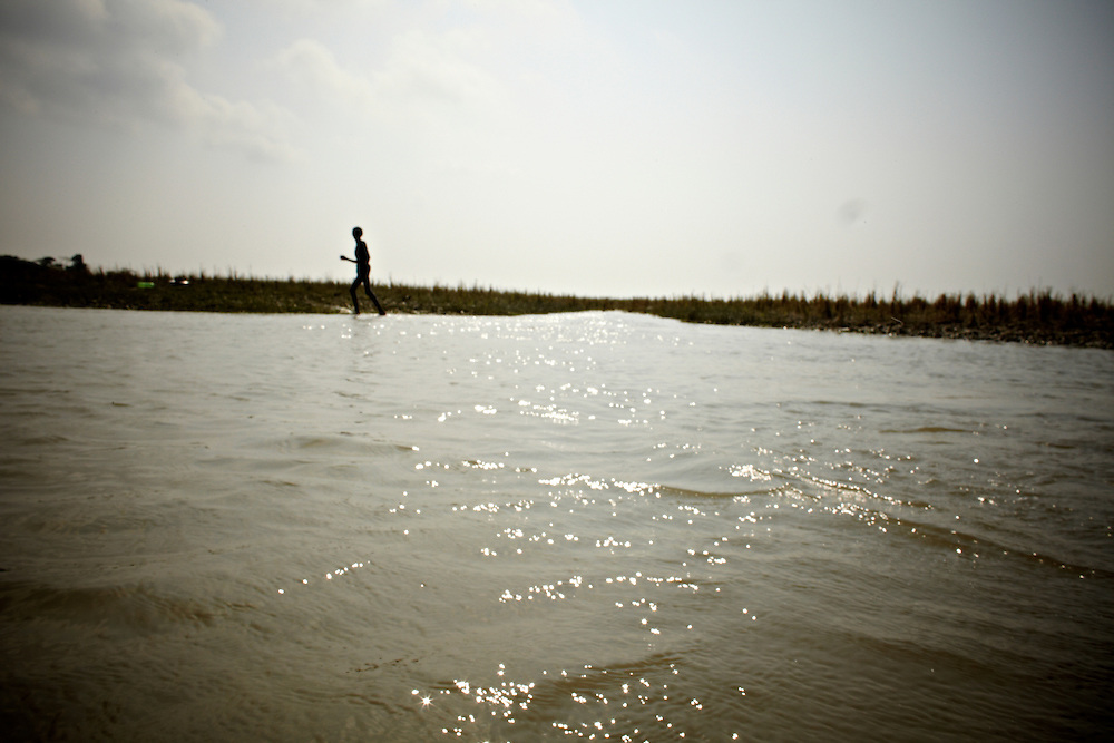 A boy getting out of a canal in Chaar Kukri Mukri..This area in the south of Bangladesh has been called ground zero of climate-change due to heavy river and ocean erosion. The lowlying area is also hugely affected by cyclones and rising sea-levels...By the Mouth of Ganges, at the Bay of Bengal is the Island of Bhola. This home of about two million people is considered to be ground zero of climate change. Half the island has disappeared in the past 40 years, and according to scientists the pace is not going to slow down. People pack up and leave as the water get closer. Some to a nearby embankment, while those with enough money move further inland, but for most life move on until the inevitable. It's always about survival for the people in one of the worlds poorest countries...Photo by: Eivind H. Natvig/MOMENT
