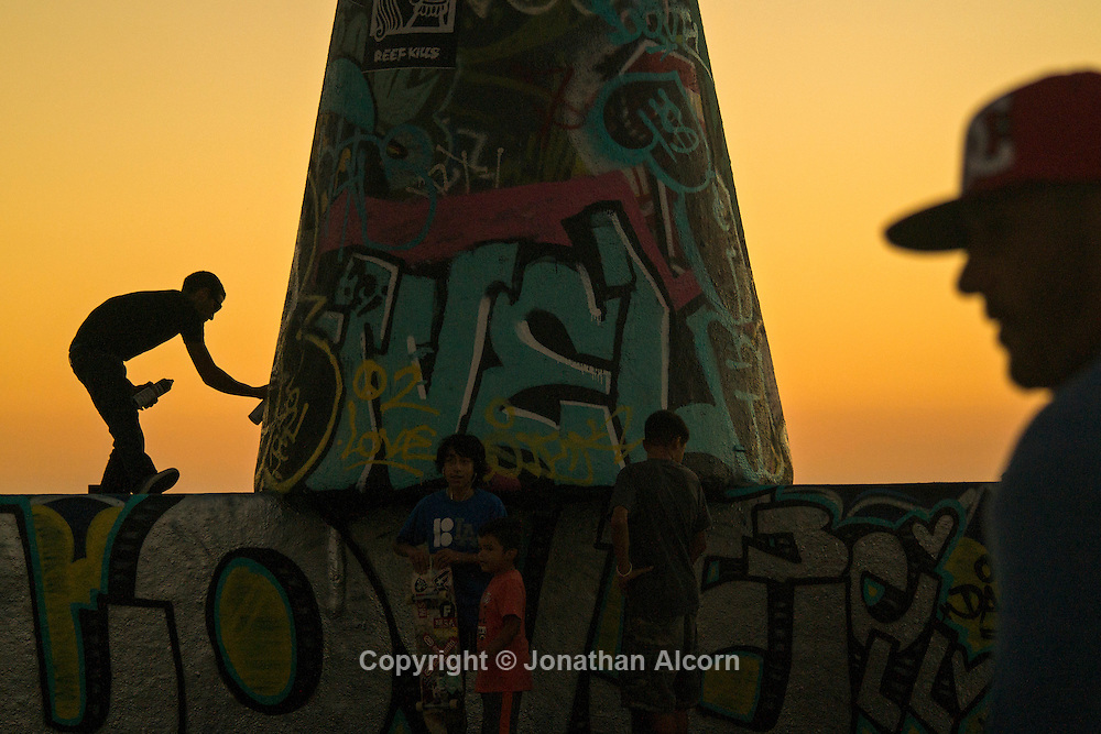 A man spray paints a portion of the Venice Public Art Walls at dusk. The Venice Public Art Walls are a series of structures on the sand in Venice Beach, California where artists can paint murals on weekends with a valid permit.