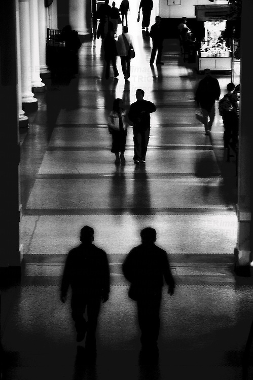 Figures walking in a railway station
