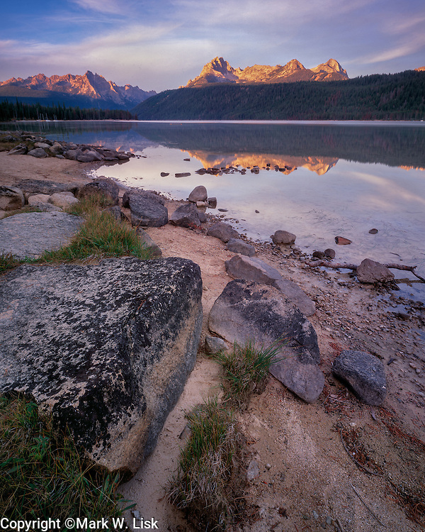 Sunrise on the Sawtooth Peaks reflects into the tranquill water of Redfish Lake, Idaho.
