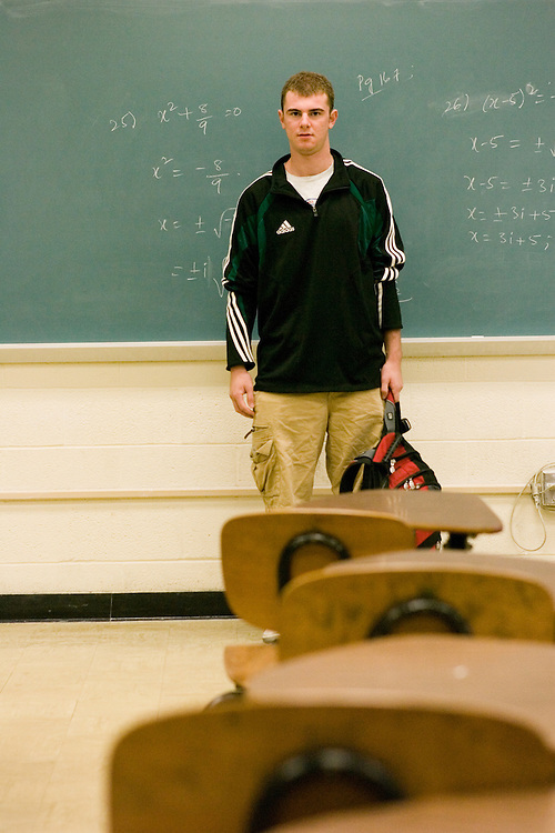 Ryan Flynn poses for a portrait in a math classroom.
