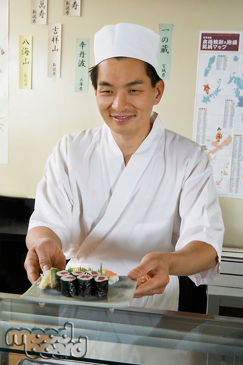 Sushi chef holding plate of sushi in restaurant