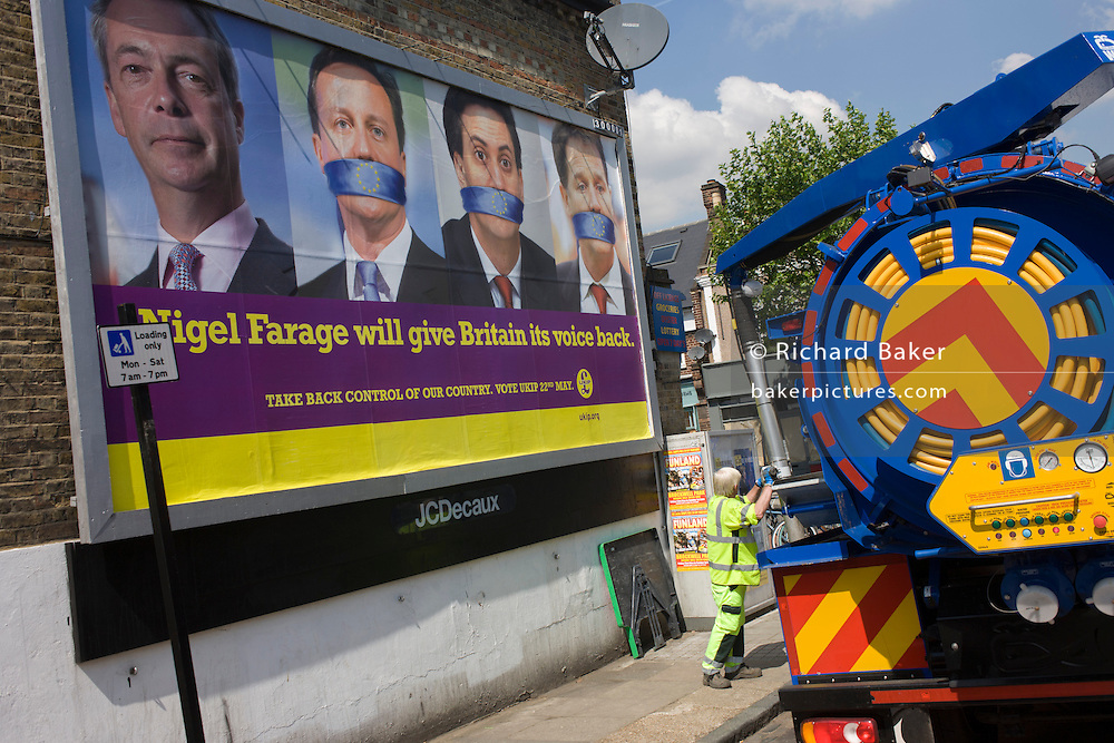A council worker empties drains near an anti-EU membership 'UK Independence Party's (UKIP) political billboard shows leader Nigel Farage and a gagged Prime Minister David Cameron, Labour party leader Ed Milliband and (coaltion) Deputy PM Nick Clegg - all silent against a bullying European Union, seen in East Dulwich - a relatively affluent district of south London. The ad is displayed before European elections on 22nd May.