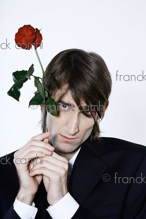 studio shot portrait of a young funny expressive thin and tall man on isolated background holding a rose