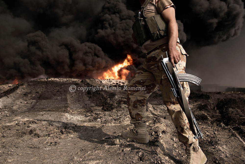 Iraq, Qayyara: An Iraqi army fighter walks by a set on fire by IS crude oil field on October 2016. Alessio Romenzi