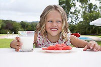 Portrait of girl (5-6) sitting at table with watermelon and glass of milk laughing