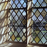Detail of stone-framed church window with diamond-leaded panes of clear or pale yellow glass throwing interesting shadows