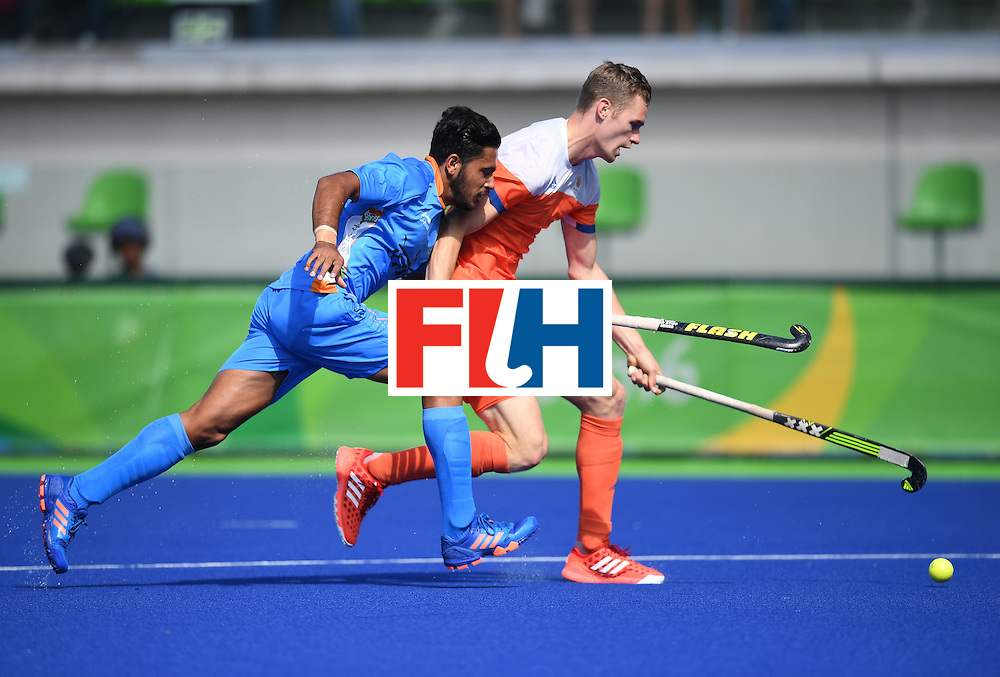 India's Harmanpreet Singh  (L) and Netherland's Mirco Pruijser chase the ball during the men's field hockey Netherland's vs India match of the Rio 2016 Olympics Games at the Olympic Hockey Centre in Rio de Janeiro on August, 11 2016. / AFP / MANAN VATSYAYANA        (Photo credit should read MANAN VATSYAYANA/AFP/Getty Images)