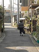 a woman walking through a residential neighborhood Yokosuka