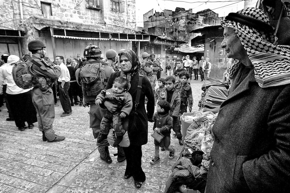 A Palestinian woman rushes her children past a group of Israeli soldiers and settlers in the old city of Hebron. Mar. 19, 2011. West Bank, Palestine.