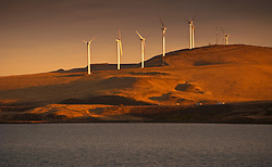Taking advantage of the abundance of wind coming up the Columbia River from the Pacific, a wind farm stands along a ridge above the river.   The river here through Umatilla Reservoir held by the John Day Dam which produces over 2000 Megawatts of electric power.  Interstate 80 and main railway route cut through the end of the ridge where it meets the river.