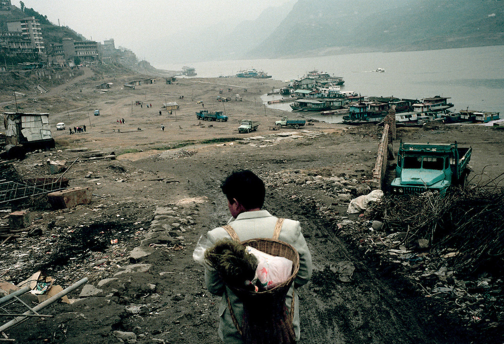 Migrant worker leaving just after the recent demolition of his town. Zigui, China. Dec 1999.