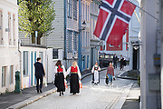 People in festive attire walk down a street in Bergen in celebration of Syttende Mai, Norway's Constitution Day, celebrated on May 17th.