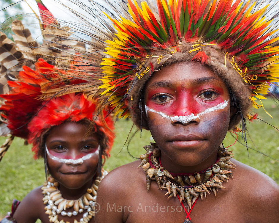 Young boy wearing a brightly coloured headdress made from lorikeet feathers, with his younger sister wearing a crown of red feathers, Goroka show, Papua New Guinea