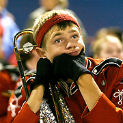 A band member is lost in his thoughts during halftime of a homecoming football game.