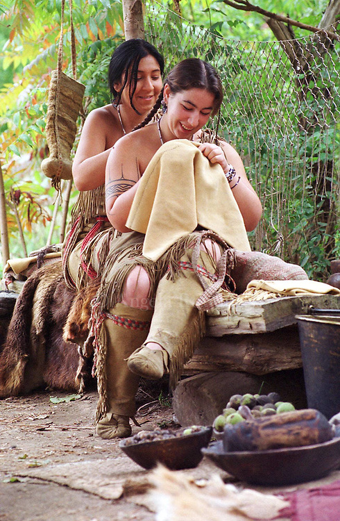 Erin Saulnier, left, braids Melanie Roderick's hair as Roderick sews a pair of men's deerskin leggings at Plimoth Plantation in Plymouth, Mass., Sunday, Oct. 10, 1999. Saulnier and Roderick, both Wampanoag Indians, interpret 17th century life at the Plantation, which also features interpretations of Pilgrim life in 1627. (AP Photo/Angela Rowlings)