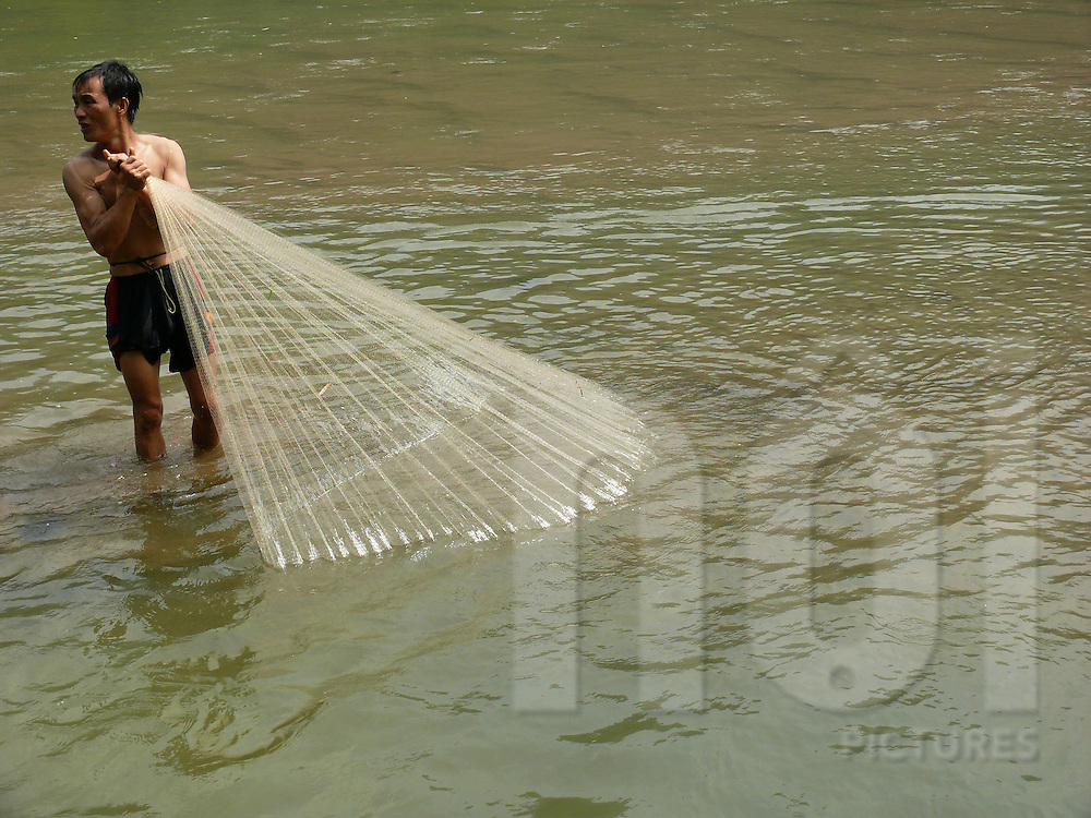 Ba Be lake in north Vietnam. Fisherman throwing a fish net.