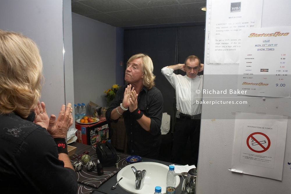 Rick Parfitt and Francis Rossi of Status Quo prepare in dressing room while on the road during European tour in Lille, France. .