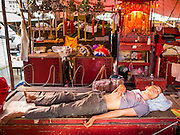 18 JANUARY 2015 - BANGKOK, THAILAND:  A member of the crew with the Sai Yong Hong Opera Troupe sleeps on stage before a performance at the Chaomae Thapthim Shrine, a Chinese shrine in a working class neighborhood of Bangkok near the Chulalongkorn University campus. The troupe's nine night performance at the shrine is an annual tradition and is the start of the Lunar New Year celebrations in the neighborhood. The performance is the shrine's way of thanking the Gods for making the year that is ending a successful one. Lunar New Year, also called Chinese New Year, is officially February 19 this year. Teochew opera is a form of Chinese opera that is popular in Thailand and Malaysia.             PHOTO BY JACK KURTZ
