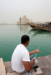 Man fishing with modern Museum of Islamic Art to rear in Doha Qatar