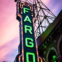 Photo of Fargo Theater neon sign at dusk in Fargo, North Dakota. The sunset provided beautiful purple and pink sky cloud colors. The Fargo Theatre was built in 1926 and is on the National Register of Historic Places. The Fargo Theatre is currently a popular venue for films, movies, concerts, plays and other live events. Photo is vertical and was taken in 2011.