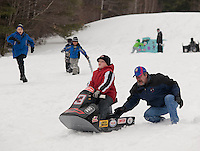 """Joey Blake gets a little extra boost from his dad Bob Blake to make it to the finish line during the annual cardboard derby race hosted by Gilford Parks and Recreation on Wednesday morning.  Blake's Dale Earnhardt tribute Sea Doo came in third for the """"Biggest Dud"""" category.    (Karen Bobotas/for the Laconia Daily Sun)"""