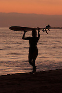A woman carries her surfboard after surfing at San Onofre Beach, San Onofre, CA on Wednesday evening, July 28, 2004.