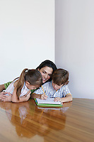Mother assisting son (7-9) and daughter (5-6) doing homework