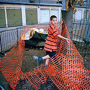 A boy plays with netting left by council builders on the Heygate estate prior to redevelopment. Part of a personal project about the estate and wider area called 'Elephant'