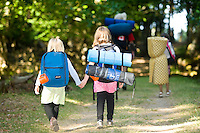 Two young campers hold hands while strolling along to their campsite on Sidney Island, just off the southern tip of Vancouver Island.  Sidney Island Marine Park, Sidney, Southern Vancouver Island, British Columbia, Canada.