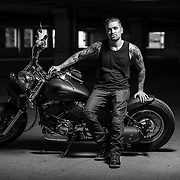 Young biker is posing next to his cool motorcycle.