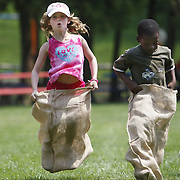 Chappaqua, NY / 2008 - Rachel Lawrence, 6, left, and Adonis Morton, 7, participate in the potato sack races at the 12th Annual Chappaqua Family Fun Day in downtown Chappaqua July 26. ( Mike Roy / The Journal News )