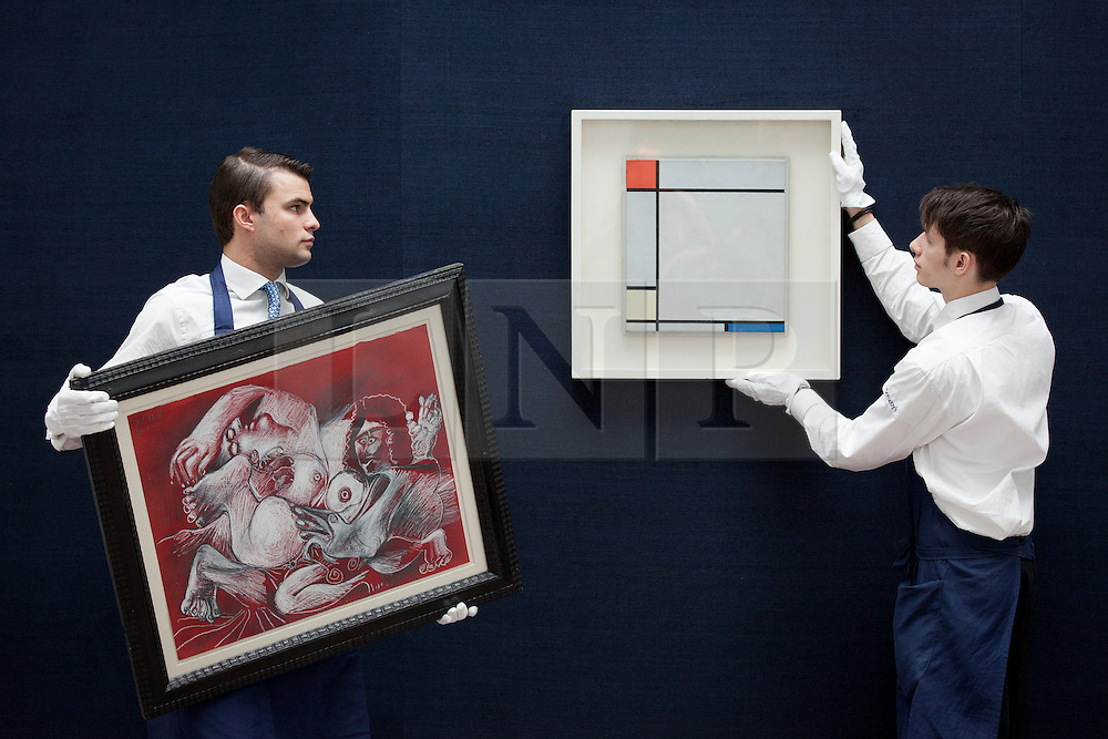 © Licensed to London News Pictures. 14/06/2013. London, UK. Sotheby's employees are seen with 'Composition with Red, Yellow and Blue' (1927, est. GB£4,500,000-6,500,000) (left) by Dutch painter Peit Mondrian and 'Etreinte' (est. GB£1,5000,000-2,000,000) by Spanish artists Pablo Picasso at the press view for a Sotheby's auction in London today (14/06/2013). The Impressionist and Modern Art Evening Sale takes place on the 19th of June 2013 at Sotheby's New Bond Street premises.  Photo credit: Matt Cetti-Roberts/LNP