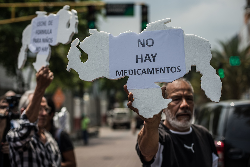 "CARACAS, VENEZUELA - APRIL 13, 2016:  Doctors, patients and their families block traffic during a protest against the hospital crisis.  This man holds a sign cut in the shape of Venezuela,  that says in Spanish, ""No medicine available"". Despite having the largest oil reserves in the world, falling oil prices and wide-spread government corruption have pushed Venezuela into an economic crisis, with the highest inflation in the world and chronic shortages of food and medical supplies.  PHOTO: Meridith Kohut for The New York Times"