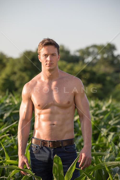shirtless muscular man standing in a field