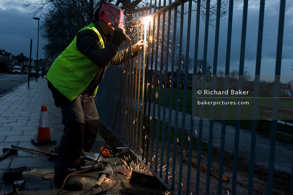 A Lambeth council contractor repairs park railings by welding uprights.
