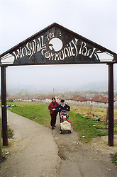 Run down community park next to council estate, Bradford; Yorkshire UK, Two women pushing toddler in buggy