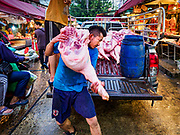 "04 DECEMBER 2018 - BANGKOK, THAILAND:  Butchers deliver sides of pork to venders in Khlong Toei market. Khlong Toey (also called Khlong Toei) Market is one of the largest ""wet markets"" in Thailand. The market is located in the midst of one of Bangkok's largest slum areas and close to the city's original deep water port. Thousands of people live in the neighboring slum area. Thousands more shop in the sprawling market for fresh fruits and vegetables as well meat, fish and poultry.     PHOTO BY JACK KURTZ"
