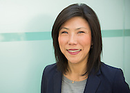 Natural headshot of a female business executive in a corporate office with blue glass background, Boulder, CO