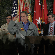 Pres. Bush, flanked by Gen. Ricardo Sanchez and Iraqi Administrator Paul Bremer, salutes troops as he spends Thanksgiving dinner with troops of the 1st Armor Division in a mess hall at Baghdad International Airport Thursday, November 27, 2003.  In a clandestine night time move President Bush, with the knowledge of only a handful of senior staff, departed his ranch in Crawford, Texas and flew through the night to spend the Thanksgiving Day holiday visiting troops stationed in the war torn country...Photo by Khue Bui