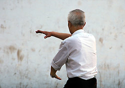 China, Taiyuan, 2007. The demanding art of tai chi keeps young and old in good shape. Mornings across China see many groups of practitioners starting the day this way..